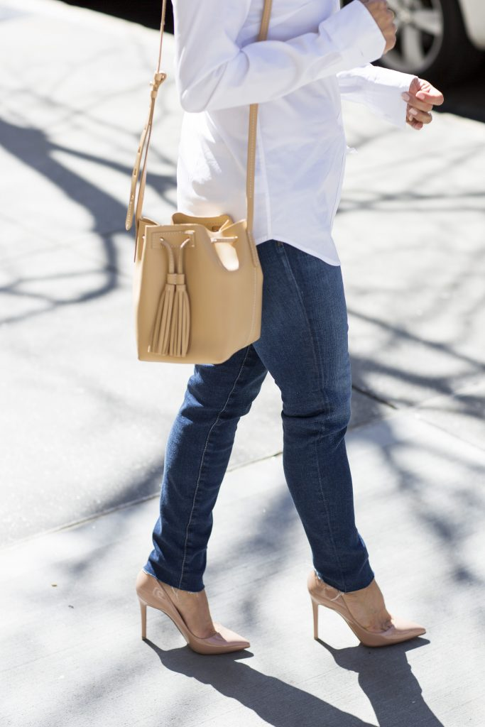 the corporate catwalk wearing a white button down shirt and denim with high heels in new york city for a casual weekend look